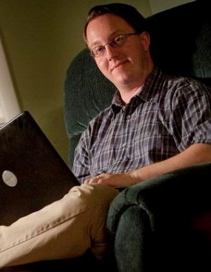Lafayette College Alumni David Walton posed in his house with his laptop computer from which he wrote his Science Fiction novel Terminal Mind